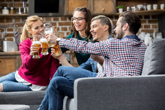 Friends drinking beer. Happy young friends drinking beer and clinking glasses at home Stock Photos