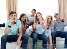 Friends drinking beer at home and watching tv Stock Images