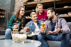 Friends drinking beer. Male and female friends drinking beer and talking on couch Stock Photography
