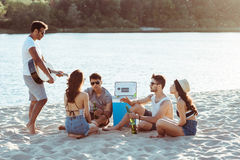 Friends drinking beer and playing guitar while sitting together on beach Royalty Free Stock Images
