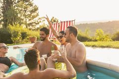 Friends drinking beer at a poolside party royalty free stock photography