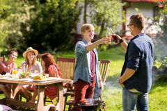Friends drinking beer at summer barbecue party Stock Images
