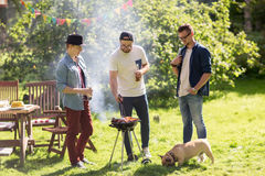 Friends drinking beer at summer barbecue party. Leisure, food, people, friendship and holidays concept - happy friends cooking meat on barbecue grill and Stock Photo