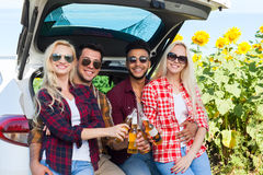 Friends drinking beer toasting clink bottles sitting in car trunk outdoor countryside Stock Photo