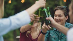 Friends drinking beer and toasting at outdoor party stock video footage