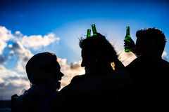 Friends drinking bottled beer at beach. Friends enjoying bottled beer at sunset on German north sea beach royalty free stock photography