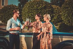 Friends drinking champagne near classic car Royalty Free Stock Image
