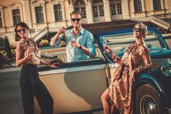 Friends drinking champagne near classic car Stock Photo