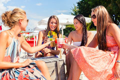 Friends drinking cocktails in beach bar Stock Images