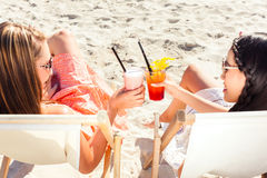 Friends drinking cocktails in beach bar Stock Photography