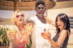 Friends drinking cocktails. Happy multiethnic friends drinking cocktails - Afroamerican men and two caucasian girls toasting drinks at party - Young people Stock Image
