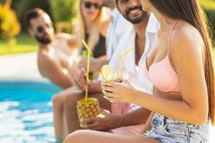 Friends drinking cocktails by the pool. Group of friends at a poolside summer party, sitting at the edge of a swimming pool, drinking cocktails and beer and stock photo