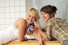 Friends drinking coffee. Two girlfriends drinking coffee a having a conversation Stock Photos