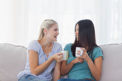 Friends drinking coffee and laughing. At home on the couch Stock Images