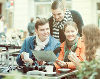 Friends drinking coffee outdoors. Group of happy adult friends drinking coffee and looking in map outdoors stock images