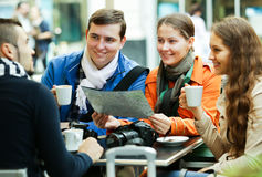Friends drinking coffee outdoors. Group of smiling adult friends drinking coffee and looking in map outdoors royalty free stock image