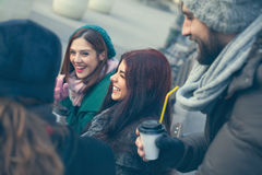Friends Drinking Hot Beverage Outdoors. Group Of Young Friends Drinking Hot Beverage Outdoors stock image