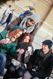 Friends Drinking Hot Beverage Outdoors. Group Of Young Friends Outdoors Drinking Hot Beverage And Using Technology royalty free stock images