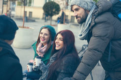 Friends Drinking Hot Beverage Outdoors. Group Of Young Friends Outdoors Drinking Hot Beverage And Using Technology royalty free stock photos