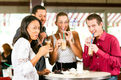 Friends drinking milk coffee and eating cake. In a bar or Cafe Royalty Free Stock Photography