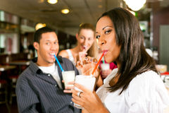 Friends drinking milkshakes in a bar Royalty Free Stock Image