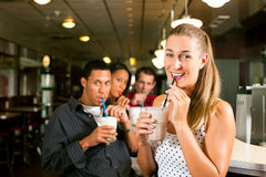 Friends drinking milkshakes in a bar. And have lots of fun; focus on the women in front stock images