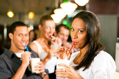 Friends drinking milkshakes in a bar. And have lots of fun; focus on the women in front stock photo