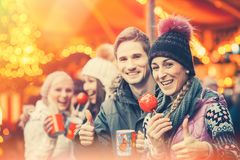 Friends drinking mulled wine and eating crystalized appels on Ge. Rman Christmas Market Royalty Free Stock Photos