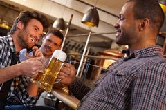 Friends drinking in pub. Happy friends clinking with beer in pub, smiling Stock Photos