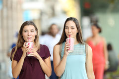 Friends drinking a takeaway refreshment. Front view portrait of two friends drinking a takeaway refreshment in the street royalty free stock photo