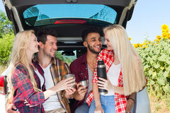 Friends drinking tea holding coffee cups thermos sitting in car trunk outdoor countryside Royalty Free Stock Image