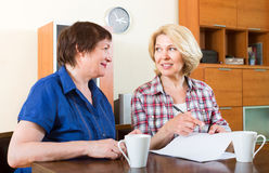 Friends drinking tea and signing documents. Two smiling friends drinking tea and signing documents royalty free stock image