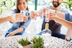 Friends drinking tequila shots outdoors. Closeup of a group of young Hispanic friends having fun together and drinking shots of tequila during a barbecue Stock Photo