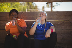 Friends drinking water after workout during obstacle course. In boot camp stock photos