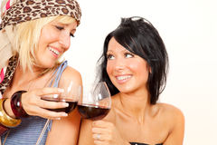 Friends drinking wine. Two cheerful girls drinking red wine while smiling to each other having fun Royalty Free Stock Photos