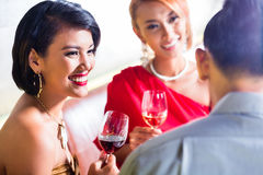 Friends drinking wine in fancy bar Royalty Free Stock Images