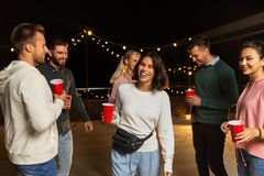 Friends with drinks dancing at rooftop party royalty free stock photography