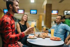 Friends drinks and eats pizza in bowling club stock images