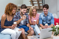 Friends with drinks looking in laptop while sitting on sofa Stock Photos