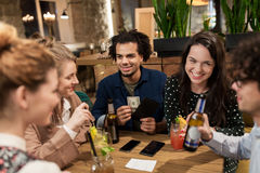 Friends with drinks, money and bill at bar Royalty Free Stock Image