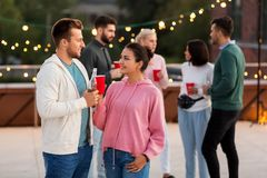 Friends with drinks in party cups at rooftop stock images