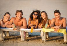 Friends with drinks relaxing on a beach Royalty Free Stock Photo