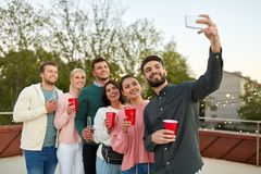 Friends with drinks taking selfie at rooftop party royalty free stock photography