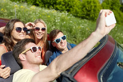 Friends driving in cabriolet car and taking selfie Stock Photography