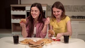 Friends Eat Fast Food. Two happy friends spending time together, eating tasty fast food in home kitchen, having nice, pleasant talk stock video footage
