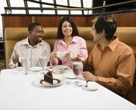 Friends eating. Small group of mid adult friends at restaurant talking and having dessert royalty free stock photos
