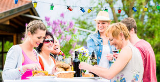 Friends eating bbq sausage and meat Royalty Free Stock Image