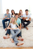 Friends eating burgers and fries. On the sofa Royalty Free Stock Photo