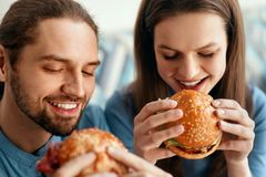 Friends Eating Burgers Indoors. Smiling People Eating Hamburgers In Fast Food Cafe. High Resolution royalty free stock photos