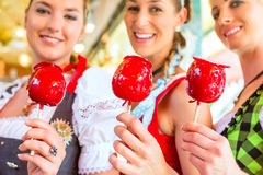 Friends eating candy apples at Oktoberfest Stock Images